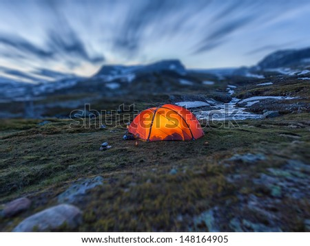 Illuminated tent in the wilderness - Miniature Effect - stock photo