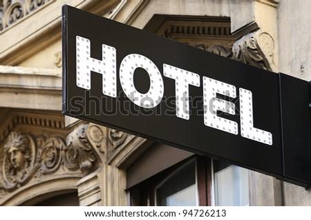 Illuminated urban hotel sign - stock photo