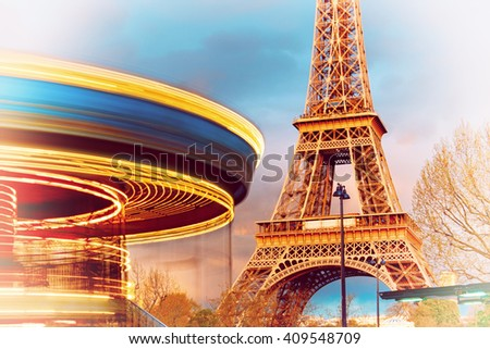 Illuminated vintage carousel rotates  in front of to Eiffel Tower, Paris, on a sunset. The metal tower reflects the setting Sun, but its own illumination is still off. This image is toned. - stock photo