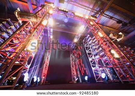 Illuminated way to boxing ring inside fight club; multi-colored lights - stock photo