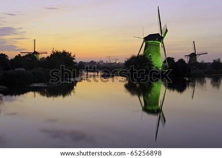Illuminated windmill at dusk Kinderdijk, The Netherlands - stock photo