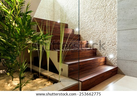 Illuminated wooden staircase in modern house, horizontal - stock photo
