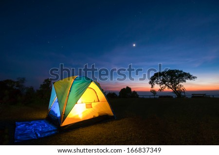 Illuminated Yellow Camping tent at Night - stock photo
