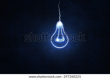 Illuminating hanging light bulb on dark background - stock photo