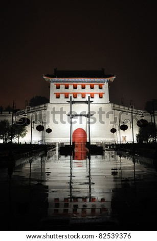 illumniated xian city wall west gate at a rainy night - stock photo