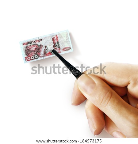 Illustration for inflation - hand with a pincer holding small banknote of Algerian dinar, white background - stock photo