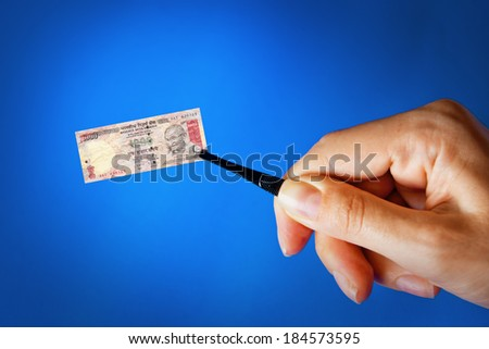 Illustration for inflation - hand with a pincer holding small banknote of Indian rupee, blue background - stock photo