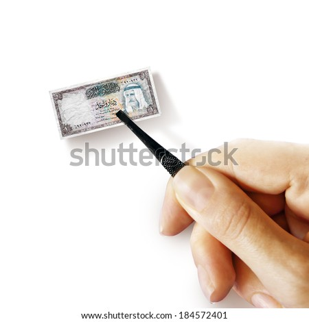Illustration for inflation - hand with a pincer holding small banknote of Kuwaiti dinar, white background - stock photo
