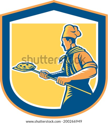 Illustration of a baker pizza maker holding a peel with pizza pie viewed from side set inside shield crest done in retro style on isolated background.