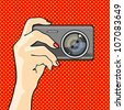 Illustration of a hand holding a photo camera (raster version) - stock photo