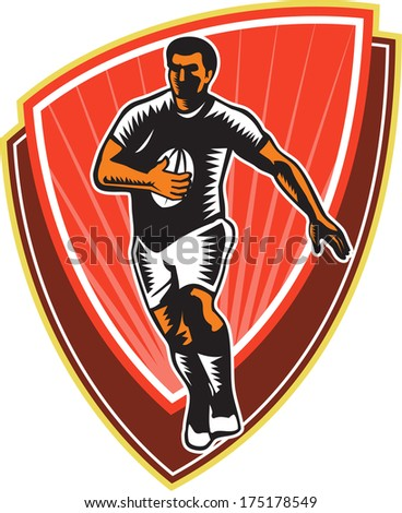 Illustration of a rugby player running with the ball in silhouette viewed from front set inside shield done in retro woodcut style.