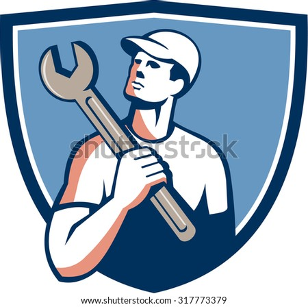 Illustration of a tradesman mechanic wearing hat holding spanner on shoulder looking up to the side set inside shield crest on isolated background done in retro style.  - stock photo