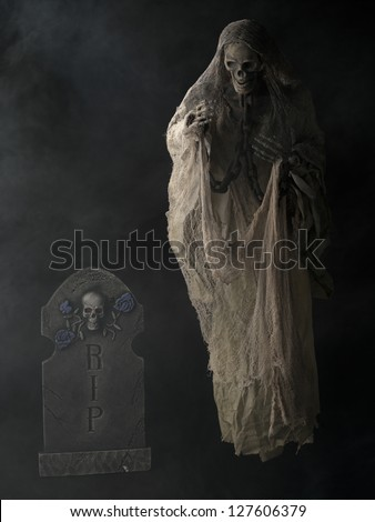 Illustration of Standing Grim reaper and Spooky Tombstone in a vertical image - stock photo