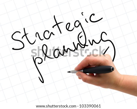 Illustration of the hand with a pen writing STRATEGIC PLANNING on the white paper background - stock photo