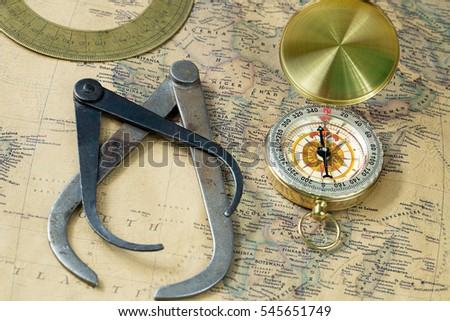 Illustrative editorial, Nizhny Novgorod, Russia - December 28, 2016. old measuring tool gold compass with cover and protractor on vintage map, macro background, compasses