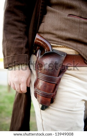 Image close up of a gun in a holster strapped to a cowboy