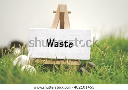 image concept white frame canvas on wooden tripod with word WASTE. Blurred and soft focus background with green grass and white stone - stock photo