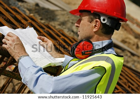 Image depicting an engineer reading plans at a construction site. - stock photo