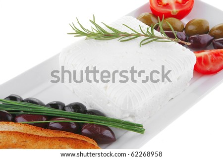 image feta cube and olive over white plate with bread