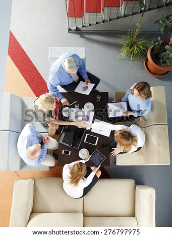 Image from above of business people sitting around conference desk and consulting. Businesswomen and businessmen using laptop and digital tablet while working on business plan. - stock photo