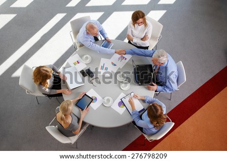 Image from above of business people sitting around conference desk and consulting. Businesswomen and businessmen using laptop and digital tablet while working on business plan.