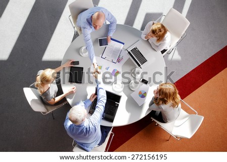 Image from above of business people sitting around the desk and working on presentation. Businessmen make a deal and shaking hands. Teamwork at office.