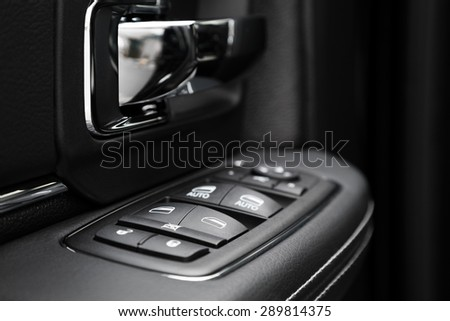 Image in closeup of a door control panel in a modern car. Arm rest with window control panel, door lock button, and mirror control.