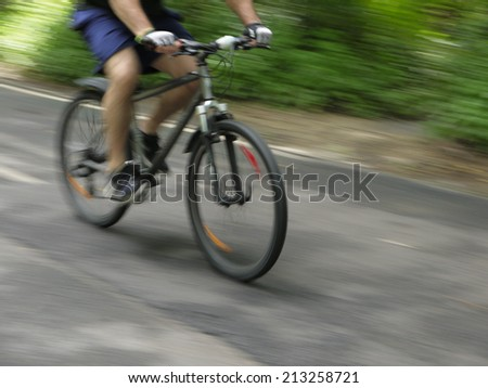 Image in motion of  bicyclists riding on country road - stock photo