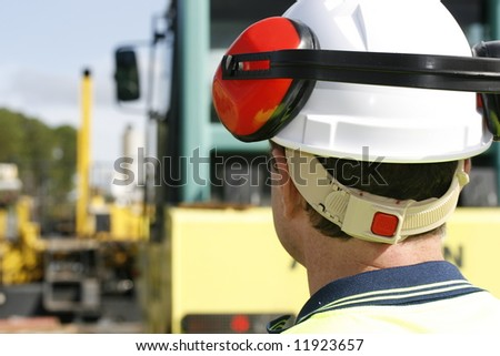 Image looking at a construction worker from behind. - stock photo