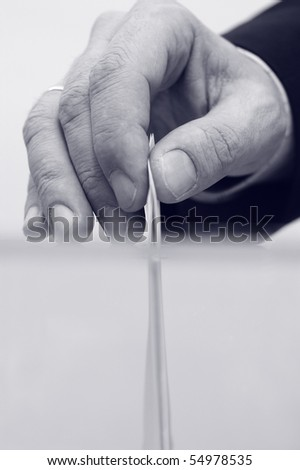 image of a ballot box and hand putting a blank ballot inside, elections concept, voting concept , blue toned - stock photo