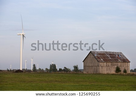 Image of a barn in wind mill farm against blue sky in the background. - stock photo
