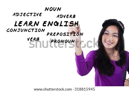 Image of a beautiful and smart teenage girl learns english and write the english materials on the whiteboard - stock photo