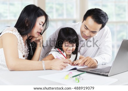 Image of a beautiful little girl studying at home with her parents and try to write on the book