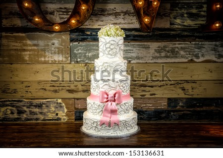 Image of a beautiful wedding cake with a rustic background - stock photo