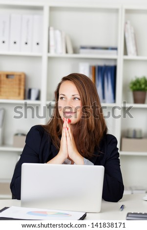 Image of a beautiful young female looking away while working on the laptop and smiling. - stock photo