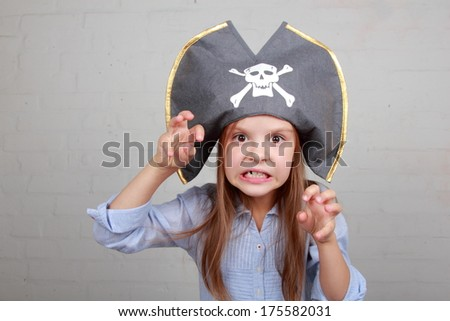Image of a beautiful young girl in the role of an evil pirate terrible on gray background on Holiday - stock photo