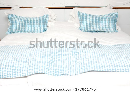 Image of a bed with blue pillow in the hotel room - stock photo
