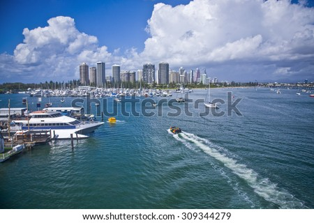 Image of a big marina and various boats with city skyline in the background