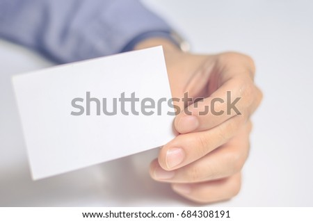 Image of a blank white piece of paper holded by a man hand. White background. Business card and name card.