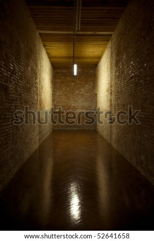 Image of a brick hallway, wood floor and wood roof lit bt a single light leading into a dead end - stock photo