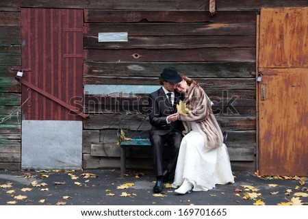 Image of a bride and a groom sitting on the bench.