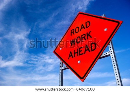 Image of a bright orange road work ahead sign against a blue sky with light clouds - stock photo