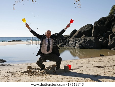 Image of a business man at the beach throwing sand in the air. - stock photo