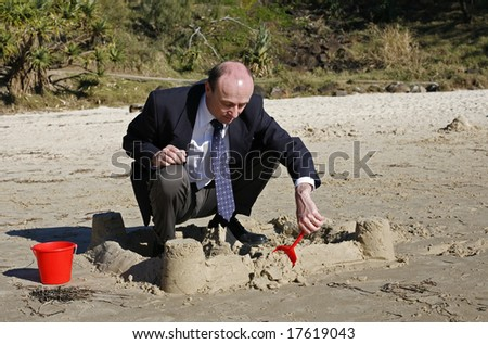 Image of a business man building a sand castle - stock photo