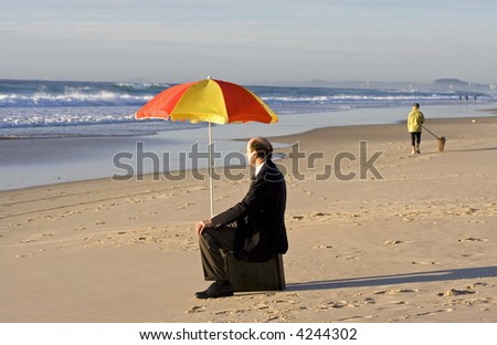 Image of a business man down at the beach sitting on his briefcase - stock photo