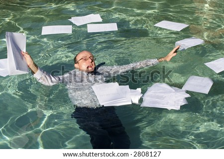 Image of a business man drowning in paperwork. - stock photo