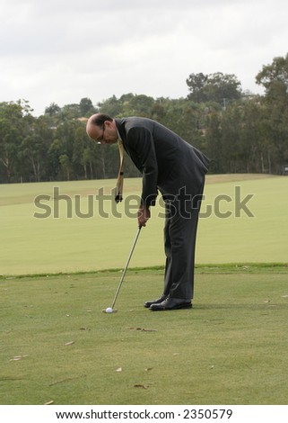 Image of a business man in a suit, about to putt out. - stock photo