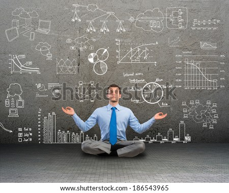 image of a business man meditating on floor, wall charts and diagrams are drawn - stock photo