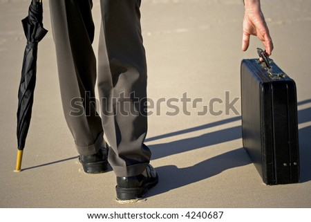 Image of a business man picking up his briefcase from the sand - stock photo