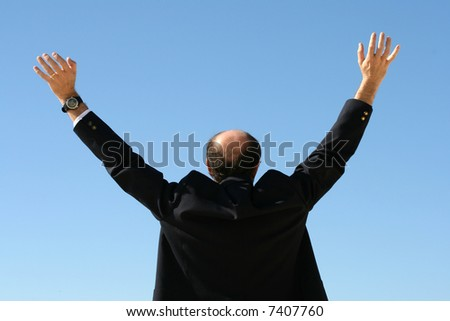 Image of a business man raising his arms. Perhaps to show he is giving up or perhaps success. - stock photo